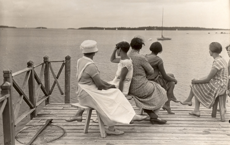 Naisia laiturilla meren äärellä